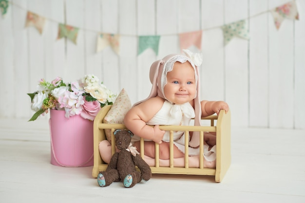 Милый забавный ребенок с ухом кролика. милая девочка 6 месяцев в постели