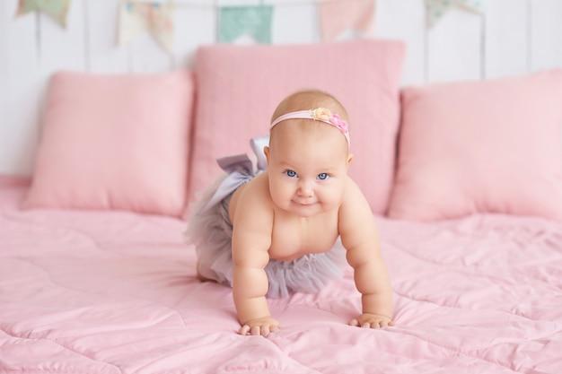 子供部屋のベッドの上の甘い面白い赤ちゃん。6ヶ月座ってクロールのかわいい女の子。
