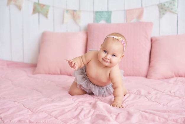 Сладкий забавный ребенок на кровати в детской комнате. милая девочка 6 месяцев сидит и ползет.
