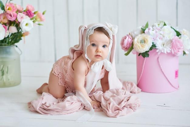 Милый забавный ребенок с ушками зайчика. милая девочка 6 месяцев в постели.
