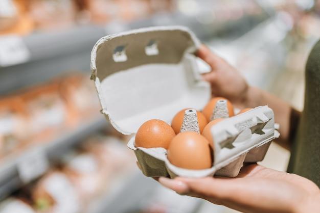 6有機卵の段ボールを保持している店の若い女性。