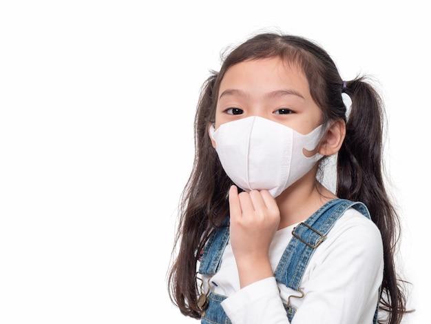 病気を広げるために衛生的なマスクを身に着けている6歳のアジアのかわいい女の子。ウイルス、風邪、または汚染の拡散の防止。