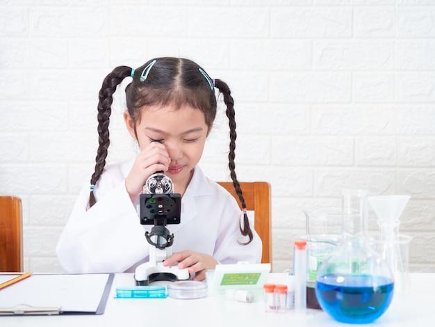 Маленькая азиатская милая девушка 6 лет старой роли играя ученого в научной лаборатории и уча использовать микроскоп. обучение и воспитание малыша.