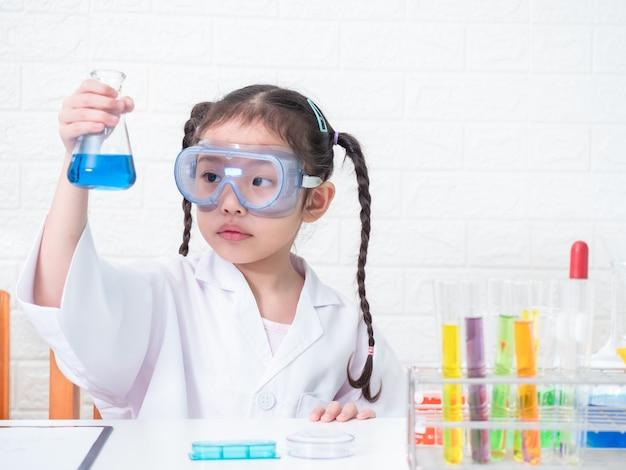 Маленькая азиатская милая девушка 6 лет старой роли играя ученого в научной лаборатории с оборудованием и смотря жидкостные химикаты в склянке.