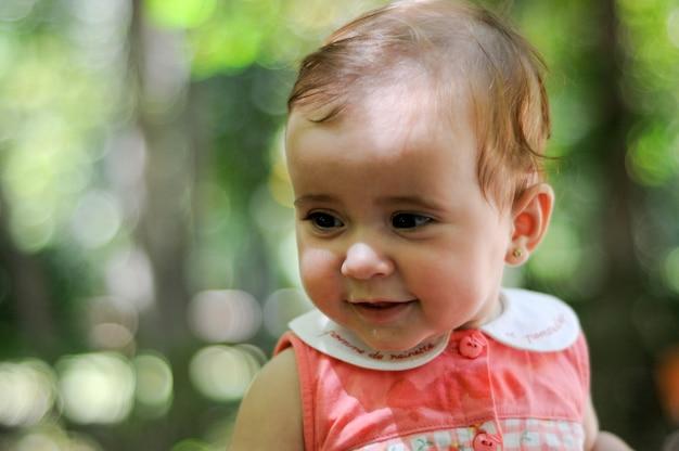 デフォーカスされた背景と屋外で笑顔6ヶ月の赤ちゃんの女の子のクローズアップの肖像画。