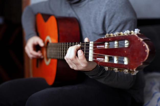 ナイロン弦で6弦アコースティックギターを弾く少女。