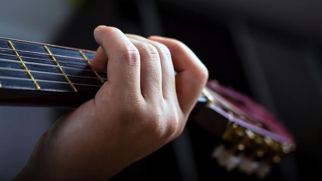 男性の手は、アコースティック6弦ギターのクローズアップで和音を保持しています。