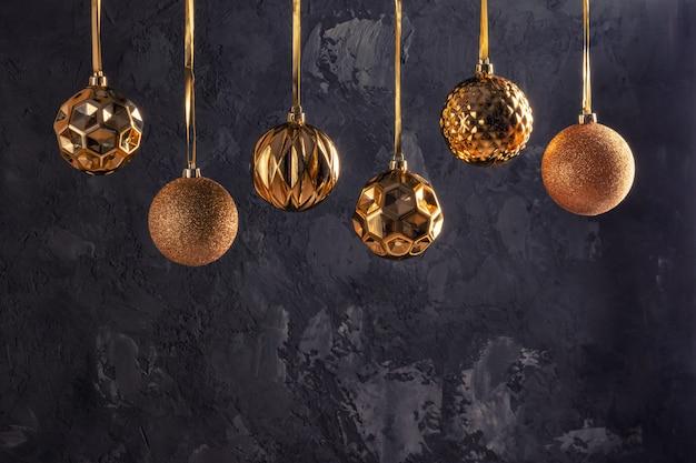 金色の6つのクリスマスボールがリボンでぶら下がっています。黒のテクスチャ背景にコピースペースを持つ美しい構図。お祝いレイアウト。