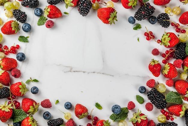 Летние фрукты и ягоды. 6 видов сырых натуральных фермерских ягод - малина, ежевика, черника, клубника, красная смородина, крыжовник. на белом мраморном столе