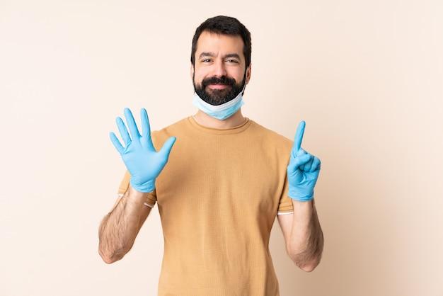 指で6を数える壁の上のマスクと手袋で保護するひげを持つ白人男