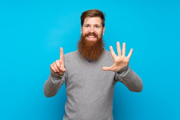 指で6を数える孤立した青の上の長いひげを持つ赤毛の男