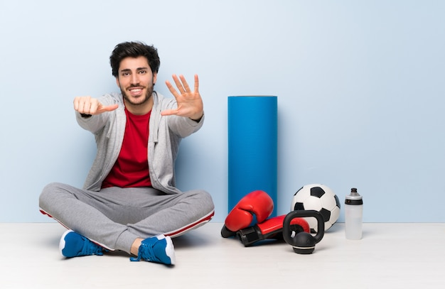 指で6を数える床に座ってスポーツ男