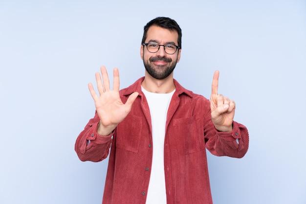 指で6を数える青い壁にコーデュロイジャケットを着た若い男