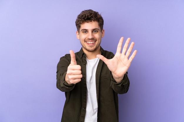 指で6を数える紫色の壁に分離された男