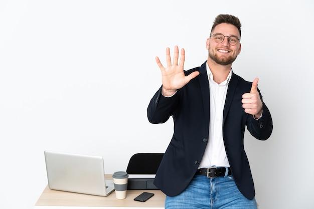 指で6を数える白い壁に分離されたオフィスの男