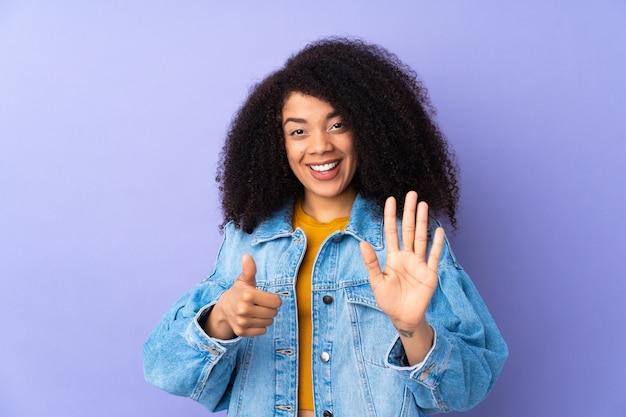 指で6を数える紫色の若い女性