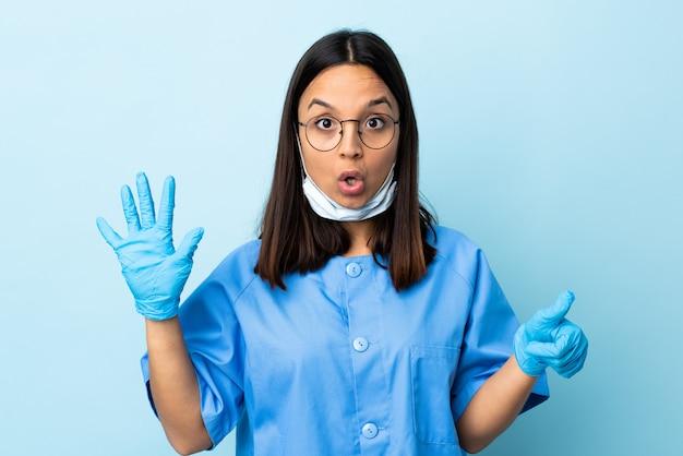 指で6を数える孤立した青い壁の上の外科医の女性
