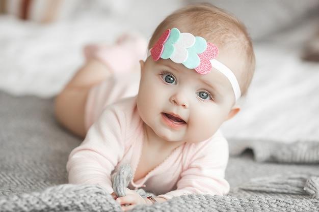 自宅の寝室でかわいい小さな赤ちゃん。屋内の幼児。 6ヶ月目の子供の肖像画。愛らしいかわいい女の子。