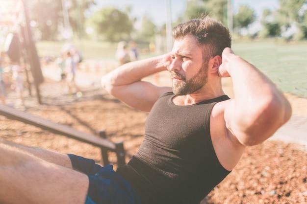腹筋運動をして運動筋肉の男。 6パックのアスリート、白人男性、屋外トレーニング。スポーツと健康的なライフスタイル。屋外でクランチをしているひげを生やした黒髪の男。