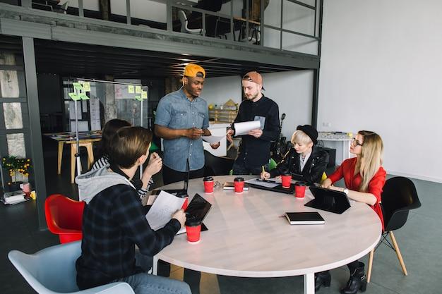 創造的な6人の若い多合理的なビジネス人々とオフィスで働く建築家