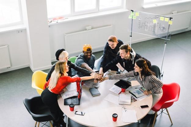 チームコミュニケーション。オフィステーブルに座って、一緒に腕を押しながら笑顔で何かを議論するカジュアルな服装で6人の若者のグループのトップビュー部分