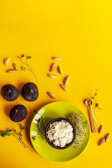 Сыр рикотта, 6 белых яиц, инжир, микро зеленый и миндаль на желтой поверхности