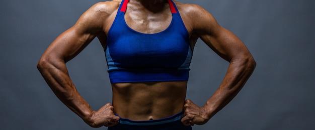 6パックの強力なハゲボディービルダー。完璧な腹筋、肩、上腕二頭筋、上腕三頭筋、胸部、彼の筋肉を曲げるパーソナルフィットネストレーナーとボディービルダーの女性。