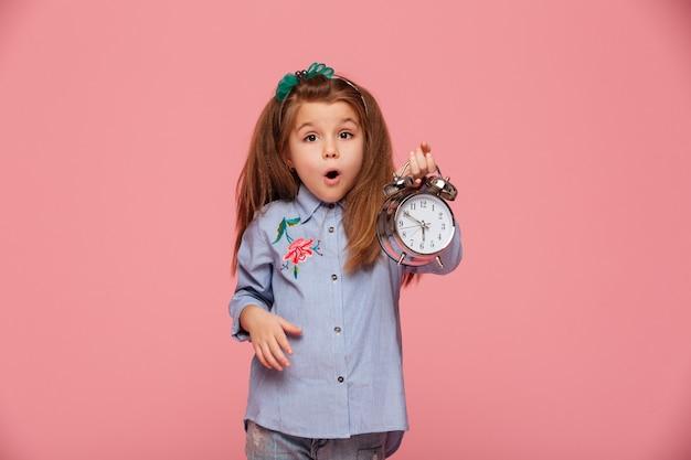 Девочка позирует с широко открытыми глазами и ртом, держа часы почти 6 в шоке или потрясен