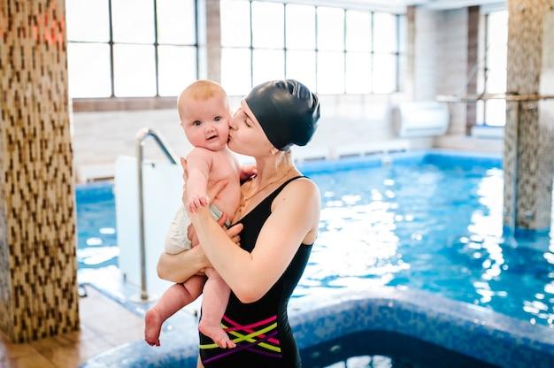 Красивая мама держит девочку 6 месяцев, младенца на руках у бассейна