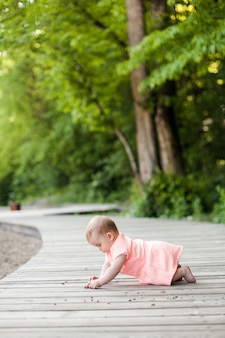 Селективный фокус счастливого 6-месячного маленького ребенка в розовом платье, ползающего по траве и играющего