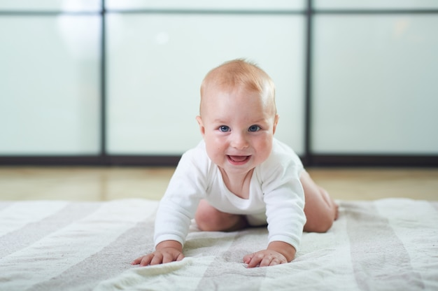 床の上でクロールかわいい6ヶ月の男の子の肖像画