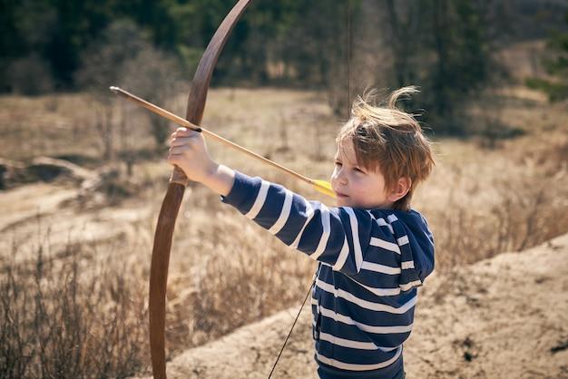 Мальчик 6 лет стреляет из лука на открытом воздухе