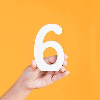 番号6を持っている手のクローズアップ