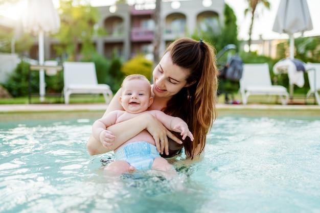 スイミングプールに立っていると彼女の生後6ヶ月の息子を保持している美しい白人の母。カメラ目線と笑顔の赤ちゃん。
