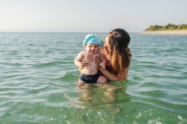 愛する6ヶ月の息子に海で泳ぐ方法を教える白人ブルネット。頭に帽子をかぶって、楽しんで、笑顔の赤ちゃん