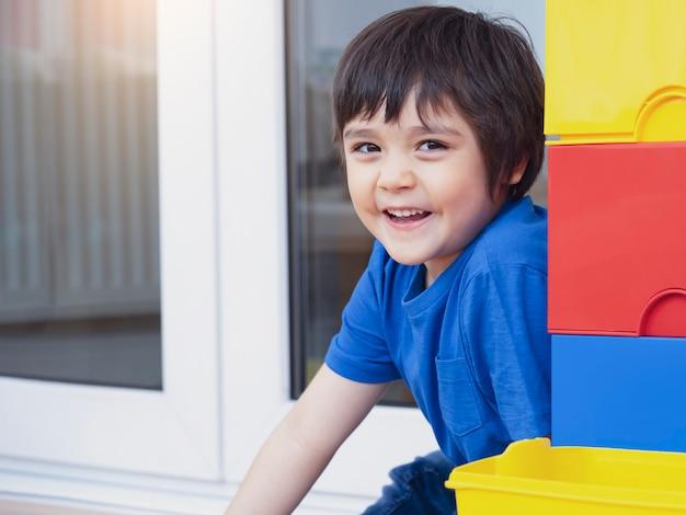 かくれんぼをしているカラフルなプラスチックの箱の横に隠れている肖像画のアクティブな子供、プレイルームで遊んで楽しんで幸せな子。週末に家でくつろぐ6歳の少年。ポジティブな子供