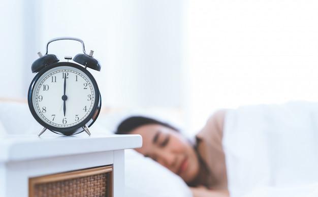 まだベッドで寝ている女性と一緒に6時を数える目覚まし時計