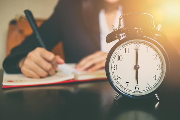 Бизнес рабочее время концепция. утро 6 часов с работой людей на заднем плане