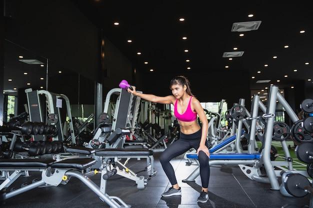 フィットネスジムで立っていると持ち上げるダンベル運動のスポーツウェアの6つのパックを持つかなりアジアの少女の肖像画。フィットネストレーニングとヨガの健康の概念