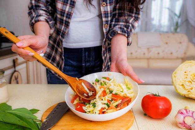キャベツ、トマト、ネギ、スパイス、オリーブオイルを使った野菜サラダの作り方の手順。ステップ6.ボウルにすべての材料を完全に混ぜます。