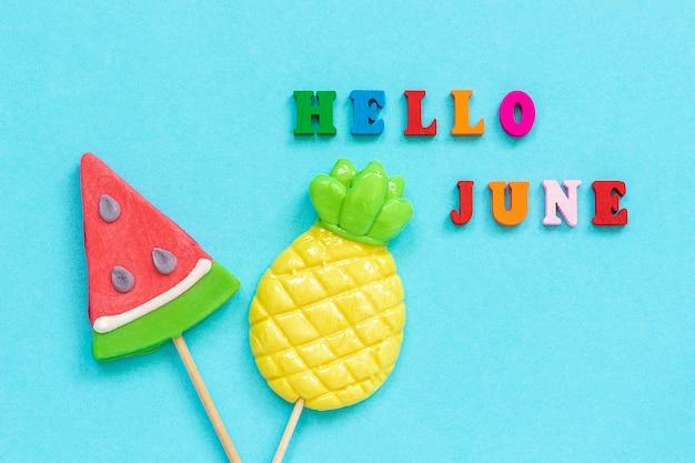 こんにちは、青い紙の背景に棒に6月のカラフルなテキスト、パイナップル、スイカのロリポップ。