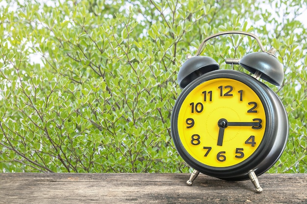 クローズアップの目覚まし時計は木の机の上の6時過ぎの四分の一を表示します