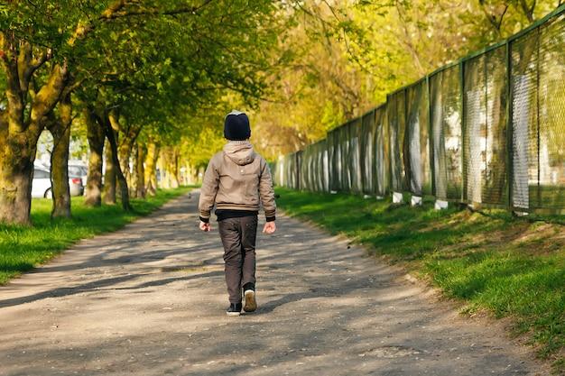 再生、ジャンプ、実行、公園で笑顔の6年のハンサムな男の子。