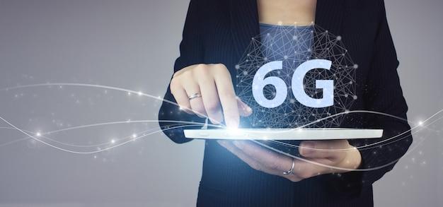 Сеть 6g интернет мобильный беспроводной бизнес. белая таблетка в руке коммерсантки с цифровой голограммой 6g подписывает на сером цвете. концепция сети 6g, высокоскоростной мобильный интернет, сети нового поколения.