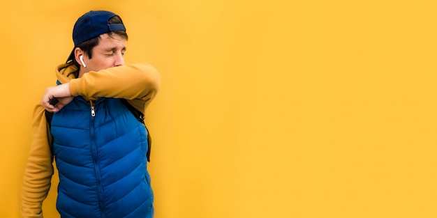 6x3 banner european man with blue clothes on sneezes into his elbow from the virus, closing his eyes. the concept of sneezing on a yellow background copyspace.