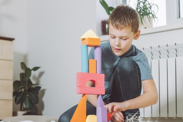 Мальчик 7-10 лет, играя дома на полу с конструктором геометрических фигур
