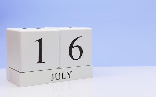 7月16日月の16日、反射、明るい青の背景を持つ白いテーブルに毎日のカレンダー。夏時間、テキスト用の空きスペース