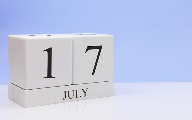 7月17日月の17日目、明るい青の背景と、反射と白いテーブルに毎日のカレンダー。