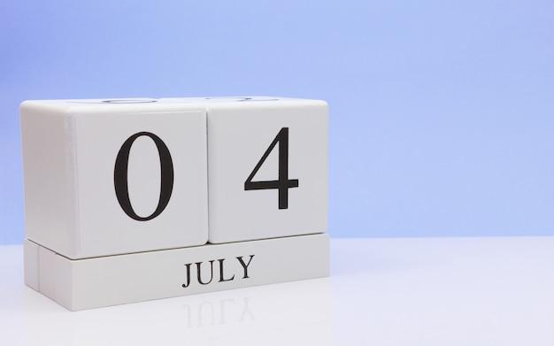 7月4日月の4日目、明るい青の背景と、反射と白いテーブルに毎日のカレンダー