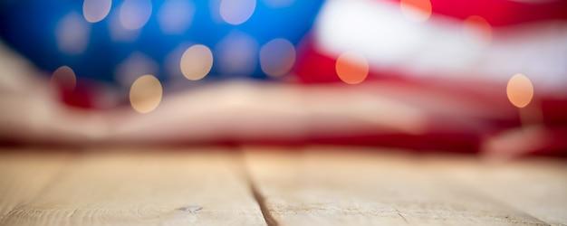 木製ヴィンテージテーブルの文字列ライトとアメリカの旗。 7月4日のお祝いのコンセプト
